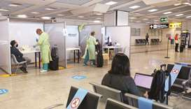 Healthcare workers collecting swab samples from passengers at the Covid-19 rapid test facility at Fi