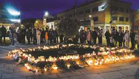 People are seen at a memorial on the Stortorvet in Kongsberg to honour the dead yesterday, the day a