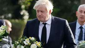 Britain's Prime Minister Boris Johnson carries a floral tribute on arrival at the scene of the fatal