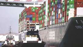 Cargo containers sit stacked on container ships at the Port of Los Angeles. Global ports are growing