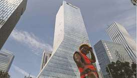 A worker walking in front of the Evergrande headquarters in Shenzhen. Evergrande has made a key offs