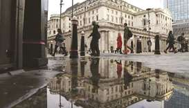 Pedestrians pass the Bank of England in the City of London. Markets now anticipate a BoE rate hike a