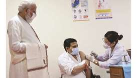 India's Prime Minister Narendra Modi watches a health worker inoculating a man with a Covid-19 vacci