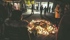 People gather to put flowers and candles at a makeshift memorial after famous Swedish rap artist Ein