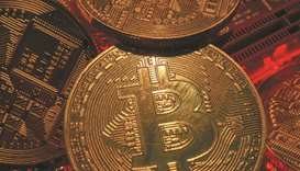Representations of the virtual currency bitcoin stand on a motherboard in a picture illustration. Th