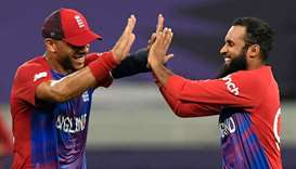 England's Adil Rashid (right) celebrates with teammate Tymal Mills after taking the wicket of West I