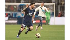 Paris St Germain's Lionel Messi in action against Marseille as a fan is seen invading the pitch. (Re