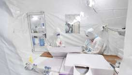 Workers in protective suits work inside a makeshift nucleic acid testing laboratory during a mass te