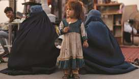A girl stands between two women at a secondhand market in Kabul, where people trying to gather funds