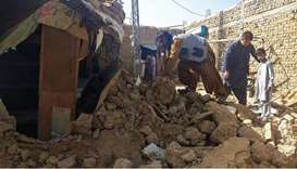 Residents gather next to the debris of their houses that collapsed following an earthquake in the re
