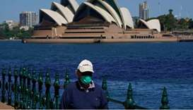 A person in protective face mask walks along the harbour waterfront across from the Sydney Opera Hou