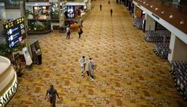 People, some of them wearing protective face masks, walk at Singapore's Changi Airport, following th