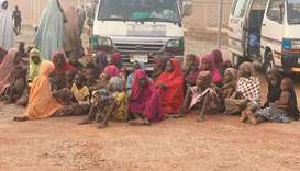 Women and children who were kidnapped in the northwestern state of Zamfara sit after being rescued b