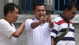 Wai Phyo (C), chief editor of the Eleven Media Group, is seen in handcuffs