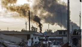 Smoke billows as soldiers from the Iraqi Special Forces take up positions as they engage Islamic Sta