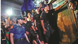 Funeral parlour workers, policemen, reporters and the relatives of a person who was killed, wait for