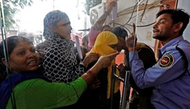 A security guard argues with a woman at a bank's entrance gate in Lucknow, India