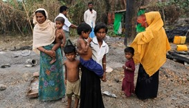 A family stands beside remains of a market which was set on fire, in Rohingya village outside Maungd