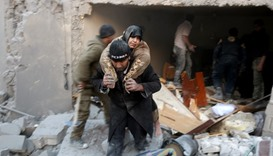 Rescuer carries a woman who was rescued from rubble of a building following airstrikes in al-Hamra