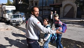 A Syrian man evacuates children from a school hit by rocket fire in Furqan neighbourhood