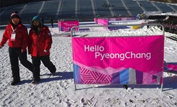 Staff walk past a banner after a practice session for the FIS Snowboard World Cup Big Air event