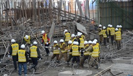 Rescue workers search at the site where a power plant's cooling tower under construction collapsed i