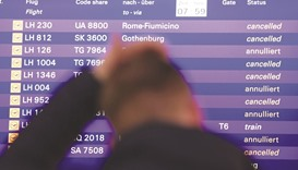 A flight passenger stands yesterday in front of a board displaying cancelled Lufthansa flights at th