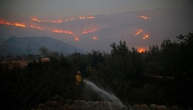 A firefighter sprays water around a house in Nataf as wildfire burns on the hills and mountains arou