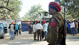 An Indian police personnel and onlookers stand near the gate of the Nabha jail