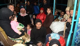 Syrian families, from various eastern districts of Aleppo, are evacuated by bus through Sheikh Maqsu