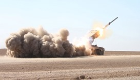 Iraqi security forces launch a rocket towards Islamic State militants