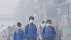 School students return home as heavy smog envelops the city in Lahore yesterday.