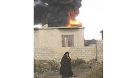 A woman walks as fire and smoke rises from oil wells, set ablaze by Islamic State militants before f