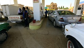 People gather to get fuel at a petrol station in Khartoum