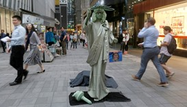 A street performer dressed as the Statue of Liberty hold photos of US presidential candidates Donald