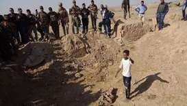 Iraqi forces search the site of a suspected mass grave containing the remains of victims of the Isla