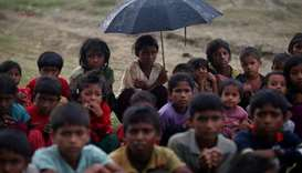 Rohingya refugee children sit in a line in the rain as they wait to receive permission from the Bang