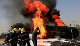 Afghan firefighters trying to extinguish the burning fuel tanker