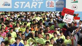 Participants taking part in Beirut's annual marathon in the Lebanese capital hold placards demanding