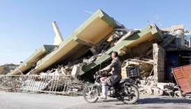 A man rides a motorcycle past a damaged building following an earthquake in the town of Darbandikhan