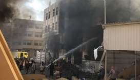 Yemeni firefighters douse flames following an explosion near a security post in the southern port ci