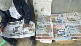 A man reads a local daily next to others with headlines about the situation in Zimababwe