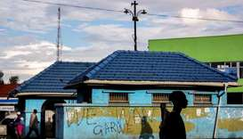 "People walk past a wall with a graffiti reading ""We want garwe (crocodile in Shona language)"" referr"