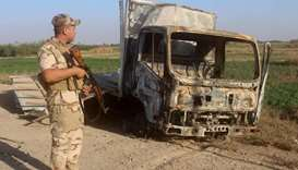A member of the Iraqi security forces looks at the wreckage of a vehicle as troops gather in the Raw