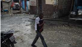 A boy walks protecting his backpack from the rain while returning from school, in a neighborhood of
