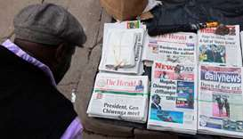A man reads the headlines of newspapers for sale on a street in Harare, Zimbabwe.  Reuters