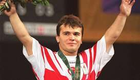 Naim Suleymanoglu of Turkey raising his arms at the medal ceremony in 1996