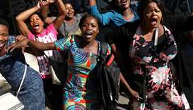 Zimbabweans celebrate in the morning sun after President Robert Mugabe resigned in Harare, Zimbabwe