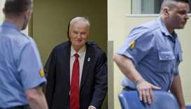 Bosnian Serb military chief Ratko Mladic (C) smiles as he enters the International Criminal Tribunal