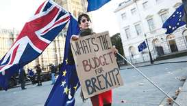 A protester holds a placard and British and EU flags outside Parliament in London yesterday.